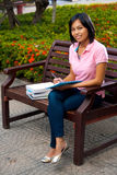 Cute College Student Bench Flowers Notepad. A cute smiling college student on a university campus bench writes into her notepad - highish angle.  20s female Royalty Free Stock Image