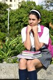 Cute Colombian School Girl And Depression Wearing School Uniform With Books Sitting