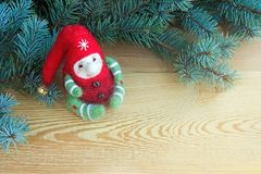 Cute colorful christmas toy elf next to fresh natural branches of Christmas tree on a wooden background stock images