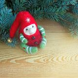 Cute colorful christmas toy elf next to fresh natural branches of Christmas tree on a wooden background stock photo