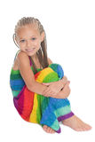 Cute in a colorful dress sitting. On the floor. Girl six years royalty free stock photos