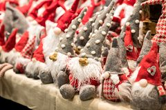 Cute colorful little Santas elves on a shelf. Wearing assorted grey and red costumes with long beards seated in rows ready for the Christmas season royalty free stock photo