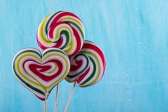 Cute colorful round lolipop and lollipop looks like a heart on turquoise  background. Cute colorful round lolipop and lollipop looks like a heart on turquoise Stock Photography