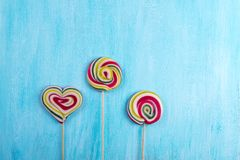 Cute colorful round lolipop and lollipop looks like a heart on turquoise  background. Cute colorful round lolipop and lollipop looks like a heart on turquoise Royalty Free Stock Photography