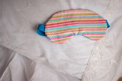 Cute colorful striped sleep mask on the white bed. Cute colorful sleep mask with the striped pattern on the background of a white bed Royalty Free Stock Image