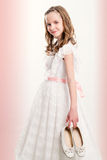 Cute Communion girl holding shoes. Close up portrait of cute Communion girl holding shoes Royalty Free Stock Images