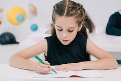 Cute concentrated schoolgirl writing in exercise book at lesson Stock Image