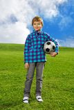 Cute confident boy with ball. 7 years old boy standing on the field with football ball Royalty Free Stock Photography