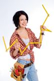 Cute construction worker. Young woman with tool belt is holding a metering rule Royalty Free Stock Photography