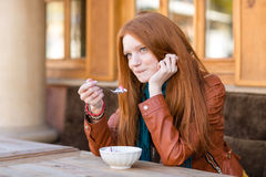 Cute content woman having breakfast and talking on cellphone Stock Images