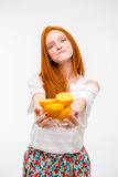 Cute content young female offers oranges and biting bottom lip. Cute content pretty candid young female offers oranges and biting bottom lip Royalty Free Stock Image