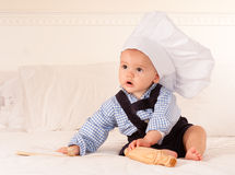 Cute cook. Cute baby with a cook hat playing with a rolling pin and wooden spoons Stock Photo