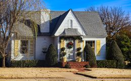 Cute cottage with yellow shutters and Christmas wreath and garland decorating entrance stock image