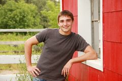 Cute Country Boy Senior Portrait. Senior Portrait of a handsome young man leaning against a red barn with a white fence in the background Stock Photo