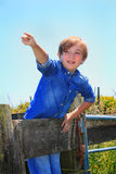 Cute Country Kid Pointing. A cute little 9 year old blond boy child in a blue shirt standing behind a wooden corral pointing to something far away. Shallow depth Royalty Free Stock Photo