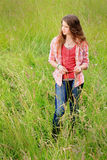 Cute Country Teen Gazing. A pretty teenage girl with long brown hair standing in a field of tall grass wearing a red plaid shirt gazing off in the distance royalty free stock photos