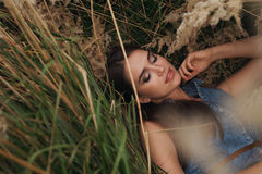 Cute countryside lady lying in tall grass Royalty Free Stock Photos
