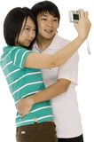 Cute Couple. A young asian couple taking their photo with a digital camera on white background stock image