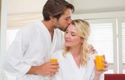 Cute couple in bathrobes drinking orange juice Royalty Free Stock Photos