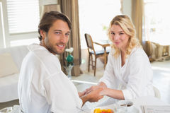 Cute couple in bathrobes having breakfast together holding hands Royalty Free Stock Photography