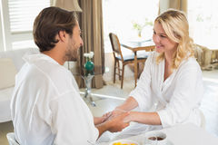 Cute couple in bathrobes having breakfast together holding hands Stock Photos