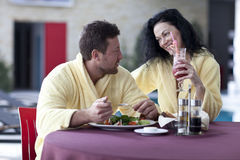 Cute couple in bathrobes having breakfast together at hotel Royalty Free Stock Photos