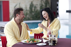 Cute couple in bathrobes having breakfast together at hotel Stock Photo