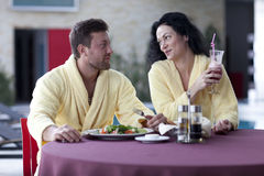 Cute couple in bathrobes having breakfast together at hotel Royalty Free Stock Photography