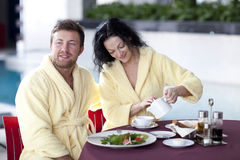 Cute couple in bathrobes having breakfast together at hotel Royalty Free Stock Photo