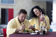 Cute couple in bathrobes having breakfast together at hotel Royalty Free Stock Image