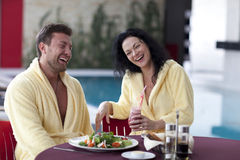 Cute couple in bathrobes having breakfast together at hotel Stock Photos