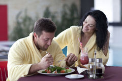 Cute couple in bathrobes having breakfast together at hotel Stock Photography