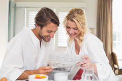 Cute couple in bathrobes having breakfast together reading the newspaper Stock Photos