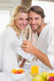 Cute couple in bathrobes having breakfast together smiling at camera Royalty Free Stock Photography