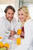Cute couple in bathrobes having breakfast together smiling at camera Royalty Free Stock Images