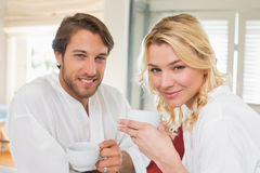 Cute couple in bathrobes having coffee together smiling at camera Stock Images