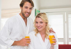 Cute couple in bathrobes smiling at camera together having breakfast Royalty Free Stock Photos