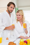 Cute couple in bathrobes smiling at camera together having breakfast Stock Photography