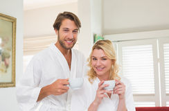 Cute couple in bathrobes smiling at camera together holding cups Stock Photos