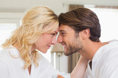 Cute couple in bathrobes touching heads Royalty Free Stock Photography