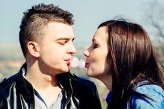Cute couple blowing bubblegum bubbles together Stock Photos
