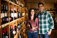 Cute couple buying a bottle of wine Royalty Free Stock Images