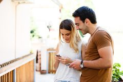 Cute young couple standing and using phone. Cute couple in cafe standing with smile and typing on phone stock photos