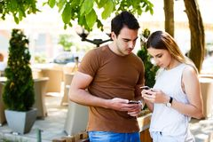 Cute young couple standing and using phone royalty free stock photo