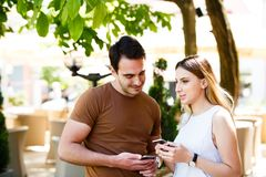 Cute young couple standing and using phone stock photo
