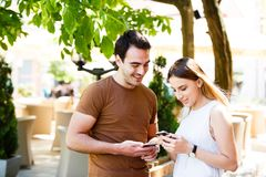 Cute young couple standing and using phone. Cute couple in cafe standing with smile and typing on phone stock images