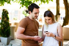 Cute young couple standing and using phone. Cute couple in cafe standing with smile and typing on phone royalty free stock photo