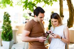 Cute young couple standing and using phone. Cute couple in cafe standing with smile and typing on phone stock photo
