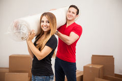 Cute couple carrying a rug. Portrait of a cute Hispanic young couple carrying a rug for their new home and smiling royalty free stock photo
