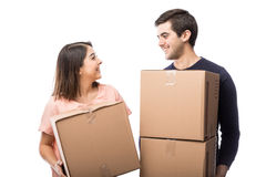Cute couple carrying some boxes. Portait of an attractive young couple carrying some boxes to their new home and looking at each other royalty free stock images